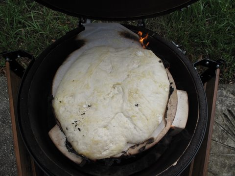 no-knead bread dough just placed in a kamado, Big Green Egg, with parchment burning