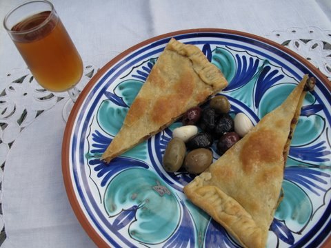 a glass of Alvear amontillado with a tapa of  olives and empanada de carne adobada