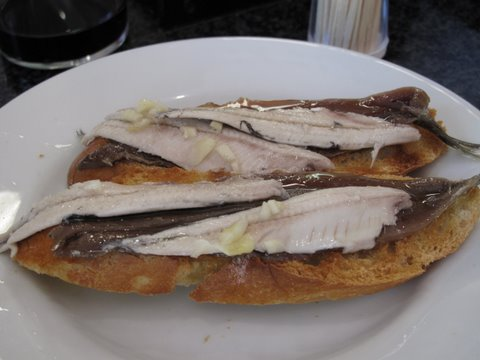 anchoa y boquerón: a cured anchovy fillet and a pickled anchovy fillet on a piece of garlic toast