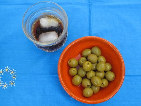 green olives stuffed with anchovies, with vermouth on ice