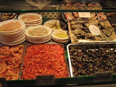 seafood on display in a tapas bar: shrimp (gambas), langostinos (prawns), angulas (baby eels), percebes (goose barnacles), etc.