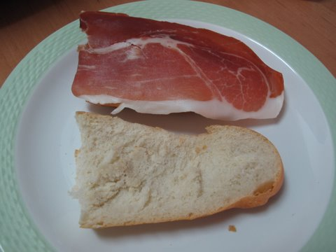 placing jamón serrano in a piece of pan de barra for a bocadillo de jamón serrano--Spanish ham sandwich