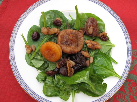 fresh spinach topped with a compote of dried fruits and nuts and Pedro Ximenez