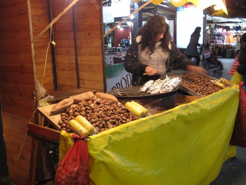 a castañera roasting chestnuts, corn, and sweet potatoes over a fire